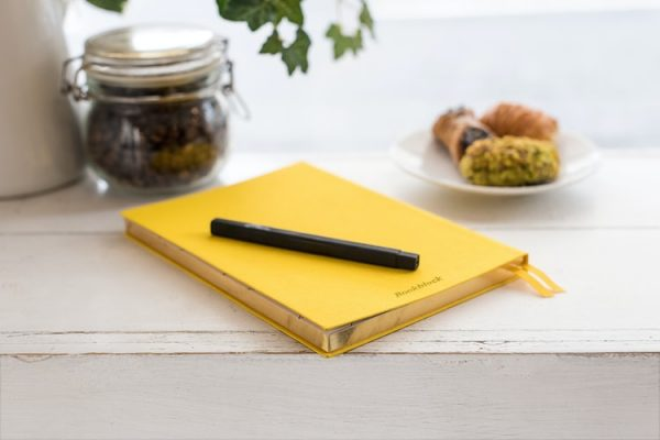 A yellow journal on a desk with a pen on top. There are many benefits of a food diary.