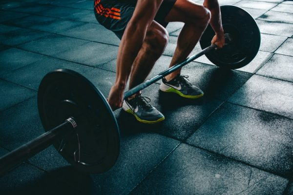 A man lifting a barbell with weights. Read these tips on how to motivate yourself.