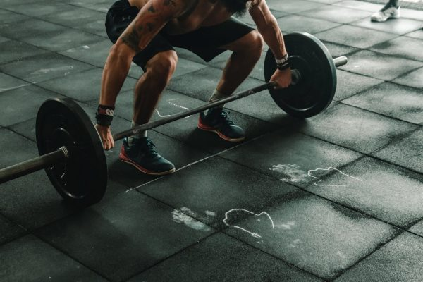 A man attempting an Olympic lift. There are many benefits of Olympic weightlifting.